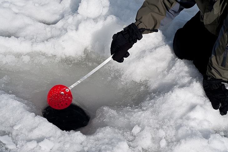 scooping out ice from a hole for ice fishing