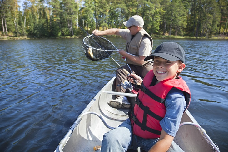 Young boy fisherman smiles while his dad takes the fish out of the net