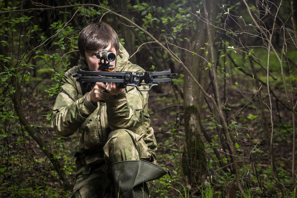 Man in camouflage suite aiming from a crossbow