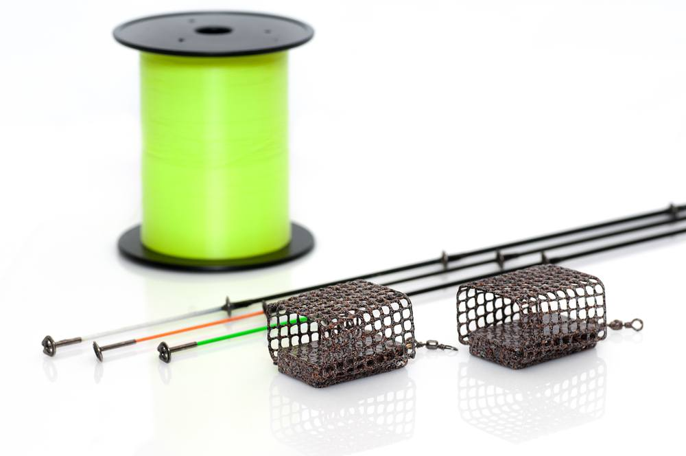 Two rectangular feeder baskets next to green monofilament fishing line spool